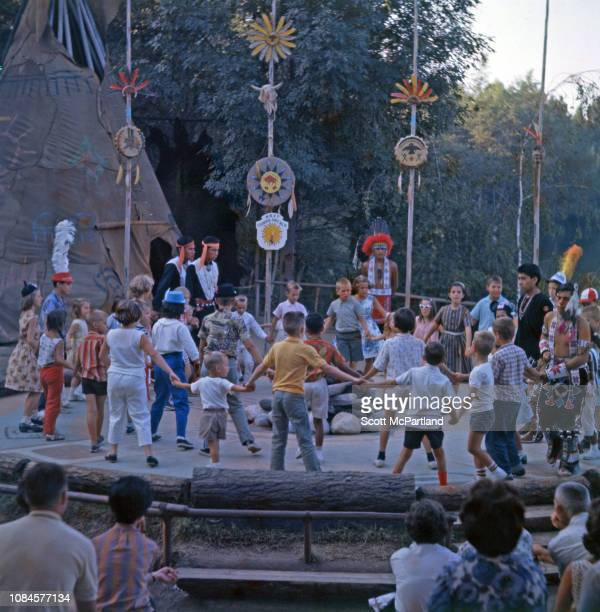 View of a circle of children as they participate with the help of costumed performers in a 'ceremonial dance' in the 'Indian Village' section of...