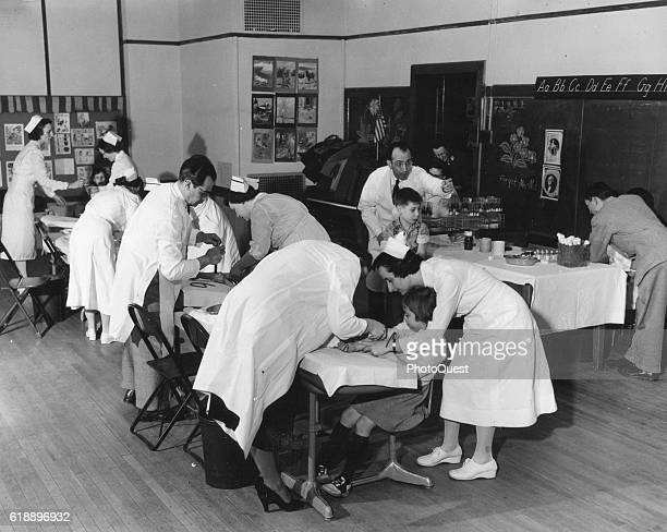 View of a classroom as children receive polio vaccinations from medical staff during Dr Jonas Salk's pilot study, Pittsburgh, Pennsylvania, 1954.
