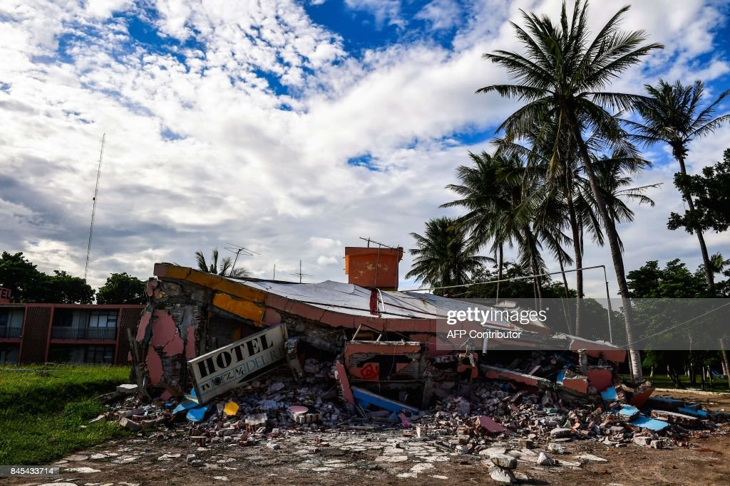 TOPSHOT - View of a collapsed hotel in Juchitan de Zaragoza, state of Oaxaca on September 10, 2017, following the 8.2 magnitude earthquake that hit Mexico's Pacific Coast on September 8. Mexican families picked nervously at the ruins of their homes Sunday as help trickled in after a huge earthquake killed 90 people. People in Juchitan were afraid to return to their homes, fearing the effects of hundreds of aftershocks -- but camped within sight of them to prevent looting. /