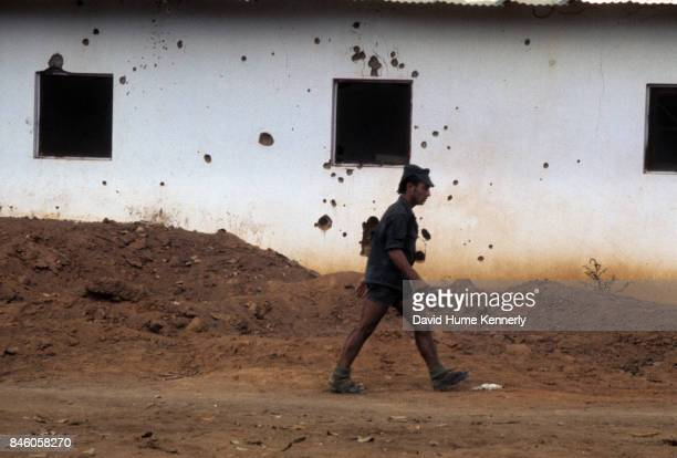 View of a Colonial Portuguese soldier as he walks along a dirt road past a house damaged by shrapnel and bullet holes during the Mozambican War of...
