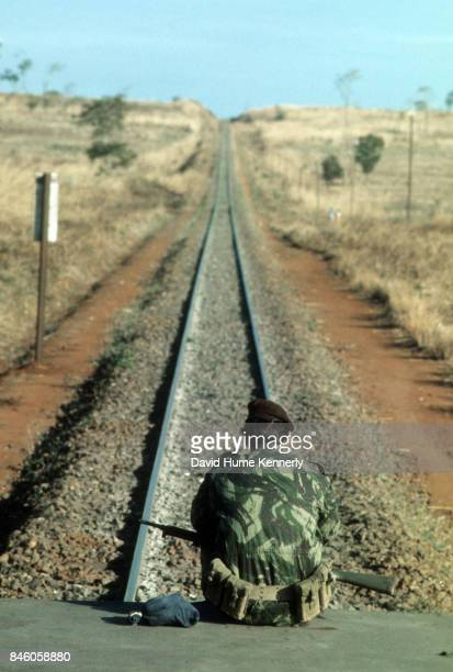 View of a Colonial Portuguese soldier sits on a flatbed train car watches over receding railroad tracks during the Mozambican War of Independence the...
