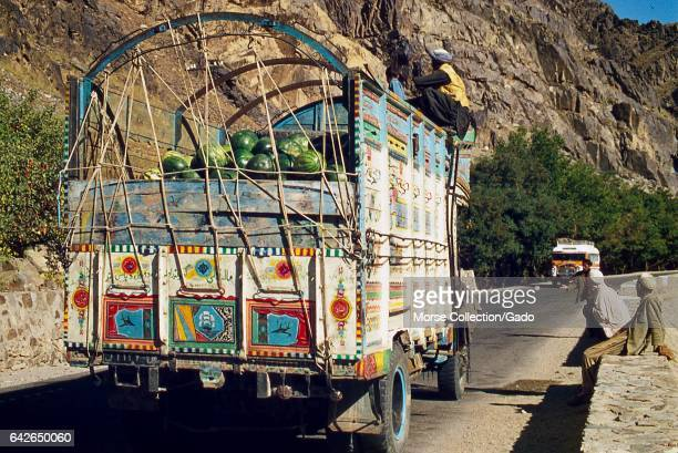 View of a colorful Pakistani-style decorated open air farm truck carrying watermelons, traveling the mountain road through Kabul Gorge, in...