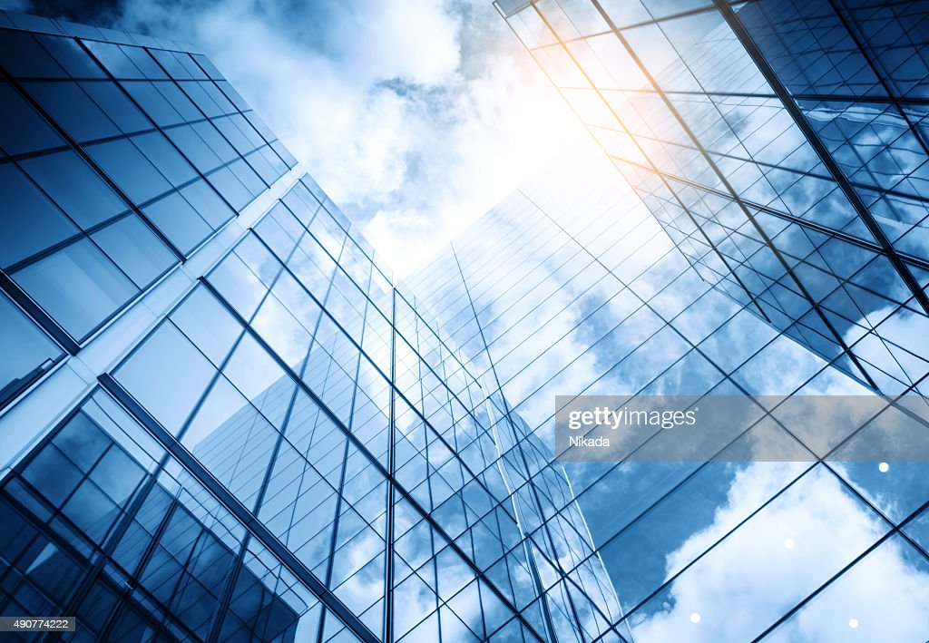 view of a contemporary glass skyscraper reflecting the blue sky : Stock Photo