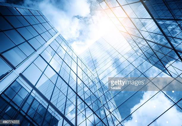 view of a contemporary glass skyscraper reflecting the blue sky - wolkenkrabber stockfoto's en -beelden