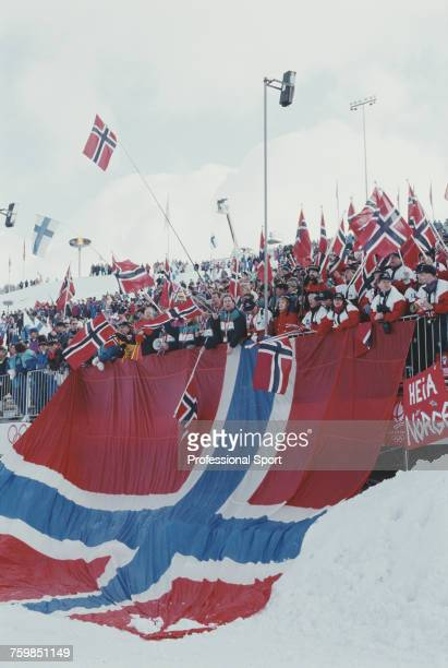 View of a contingent of Norwegian winter sports fans pictured behind a large national flag of Norway as they watch action in the crosscountry skiing...