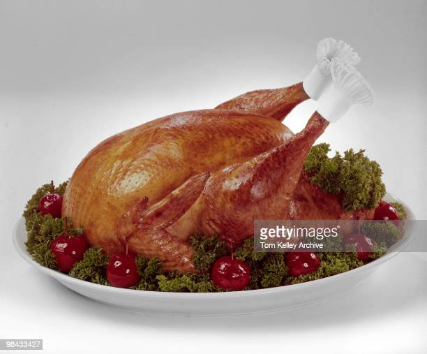 View of a cooked turkey garnished with lettue and crabapples on a serving platter 1966