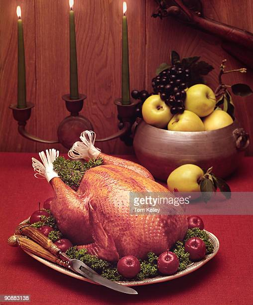 View of a cooked turkey on platter as it sits on a red tabletop with a bowl of fruit and a wooden candelabrum 1990