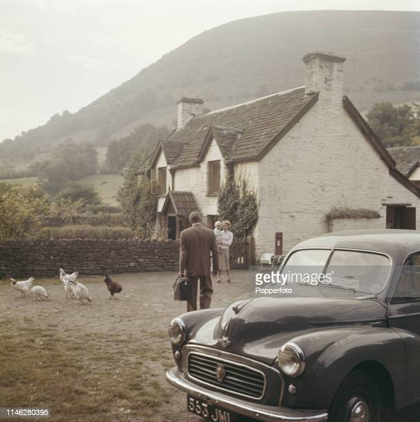 View of a country doctor leaving his Morris Minor 1000 car to call on farmer's wife Ivy Wall and child at a farmhouse whilst doing his rounds near...