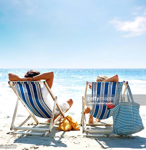 view of a couple sitting on deck chairs enjoying vacation - deck chair stock pictures, royalty-free photos & images