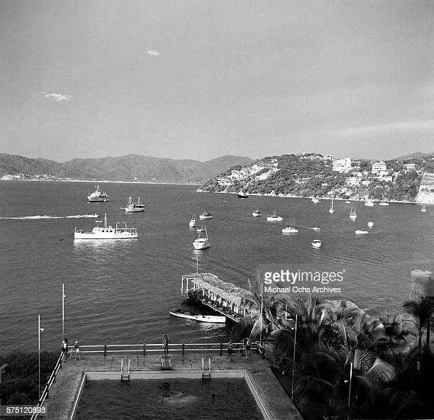 A view of a cove with boats anchored off a beach in Acapulco Mexico