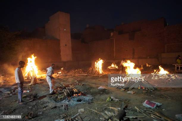 View of a crematorium ground showing funeral pyres during a mass cremation of victims, who died due to the coronavirus disease , at a crematorium in...