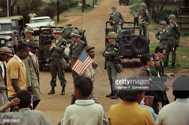 A view of a crossroads with US Army MPs and troops guarding the marchers and a row of people watching civil rights marchers walk by during the Selma...
