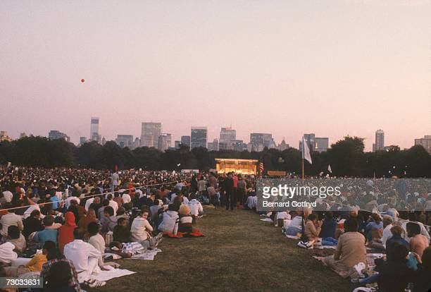 View of a crowd as they sit on the grass at a concert in the bandshell on the Sheep Meadow in Central Park New York New York early 1980s