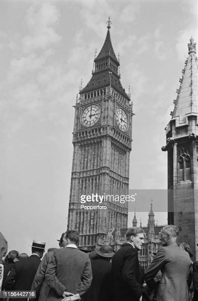 View of a crowd of Londoners and visitors standing outside Big Ben and the Palace of Westminster whilst Prime Minister Neville Chamberlain delivers a...