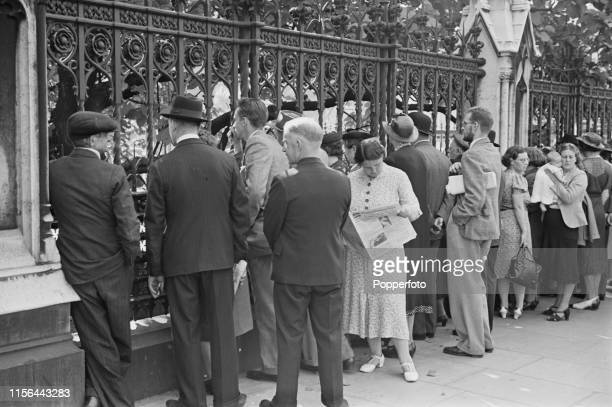 View of a crowd of Londoners and visitors standing outside the gates of the Palace of Westminster whilst Prime Minister Neville Chamberlain delivers...