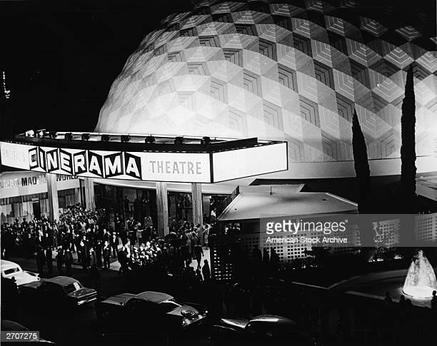 View of a crowd standing in front of the Cinerama Dome movie theatre at night Hollywood California circa 1965
