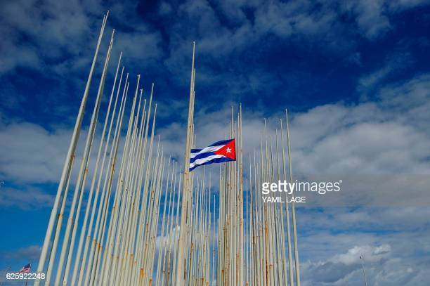 TOPSHOT View of a Cuban flag at halfmast in front of the US Embassy in Havana on November 26 the morning after Cuba's historic revolutionary leader...