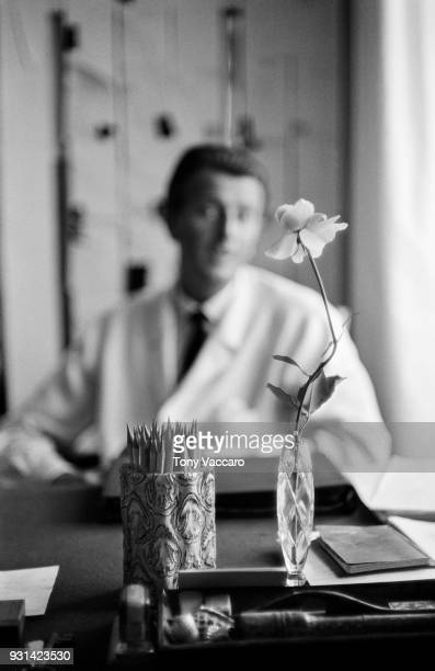 View of a cup of pencils and a single rose in a vase on a desk as French fashion designer Hubert de Givenchy sits in the background Paris France 1961...