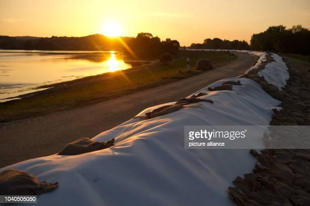 View of a dam fortified with sandbags during sunset near Hitzacker Germany 09 June 2013 PhotoSEBASTIAN KAHNERT Ein Schutzwall aus Sandsäcken steht...