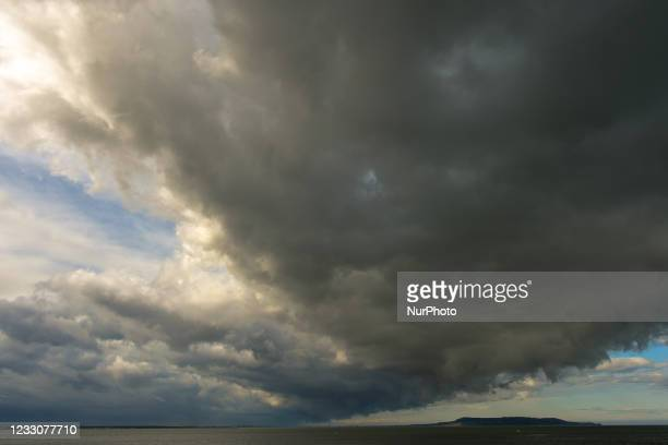View of a dark sky and approaching storm over Dublin Bay and Howth Peninsula seen from Seapoint Beach. On Sunday, 23 May 2021, in Dublin, Ireland.
