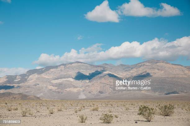 view of a desert against cloudy sky - bortes foto e immagini stock