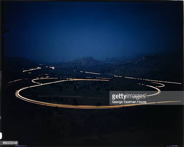 View of a desolate road at night lit up by the blur of car lights ca1950