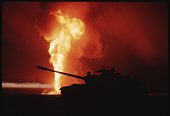 View of a destroyed iraqi tank seen in silhouette in front of a oil picture id944304958?s=170x170
