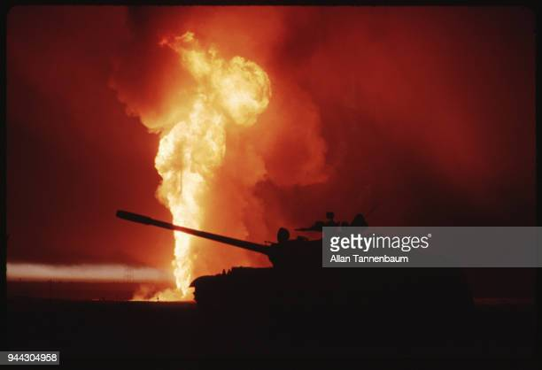 View of a destroyed Iraqi tank seen in silhouette in front of a burning oil well during the Gulf War Kuwait 1991