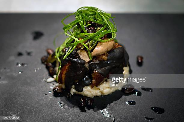View of a dish cooked by Italian chef Davide Scavin inspired in Brazilian traditional feijoada during the food and wine event Semana Mesa SP in Sao...