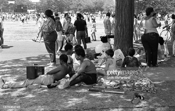 View of a family relaxing on the grass, one with a large boom box radio resting on his leg in Flushing Meadows Park, in the Corona neighborhood,...