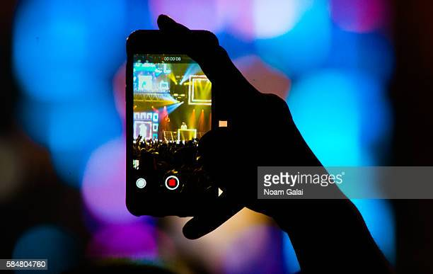 A view of a fan holding up a smartphone at The Kingdom Daddy Yankee Vs Don Omar Tour at Madison Square Garden on July 30 2016 in New York City