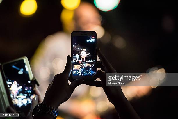 A view of a fan taking photos with a smart phone during Wyclef Jean's concert at Brooklyn Bowl on March 29 2016 in the Brooklyn borough of New York...