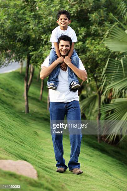 view of a father carrying his son - mid adult men stock pictures, royalty-free photos & images
