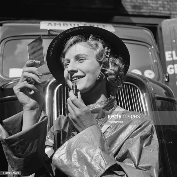 View of a female ambulance driver applying some lipstick as she waits for a call at an ambulance station in London soon after the start of World War...