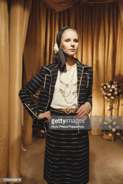 View of a female fashion model wearing a Chanel skirt suit over a pussybow silk blouse from the 1973 spring/summer collection of the House of Chanel...