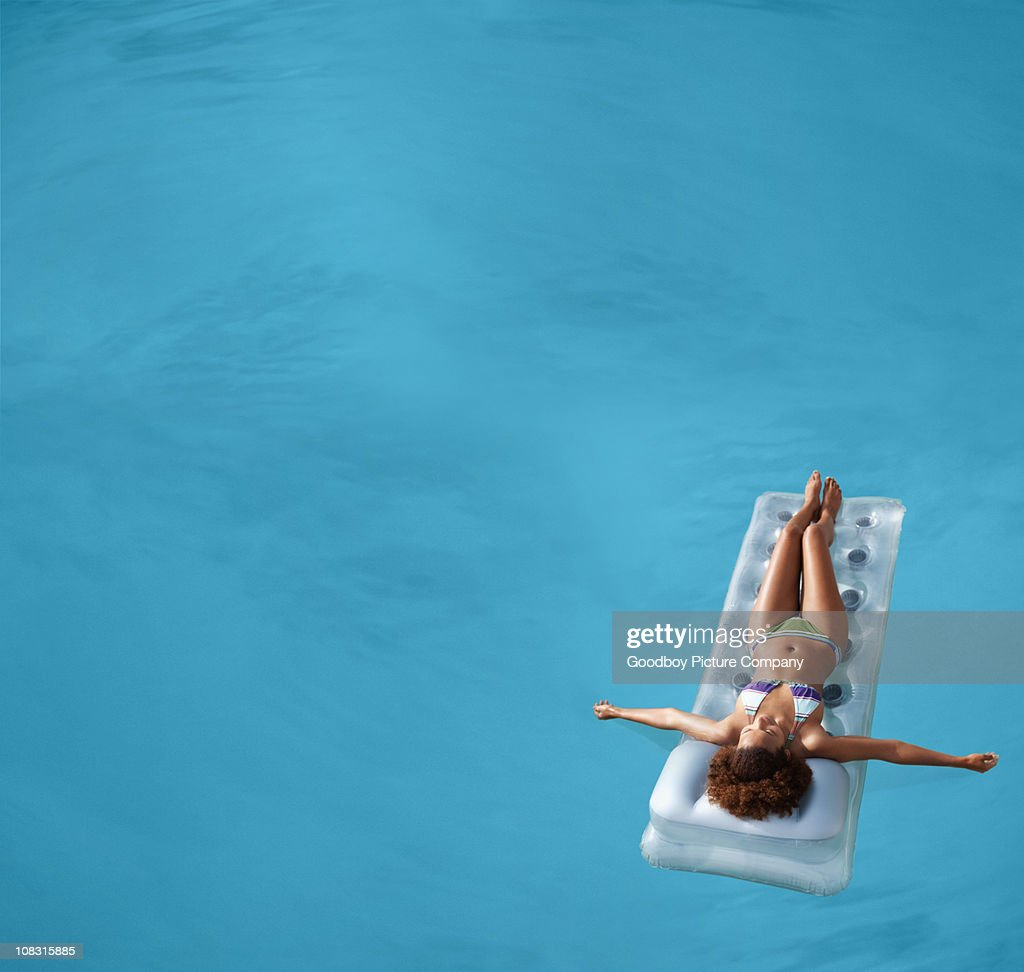View of a female floating in swimming pool : Stock Photo