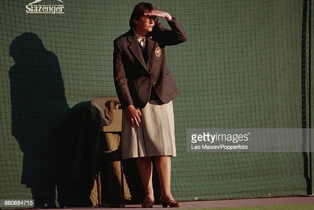 View of a female line judge shielding her eyes from the sun during play at the Wimbledon Lawn Tennis Championships at the All England Lawn Tennis...
