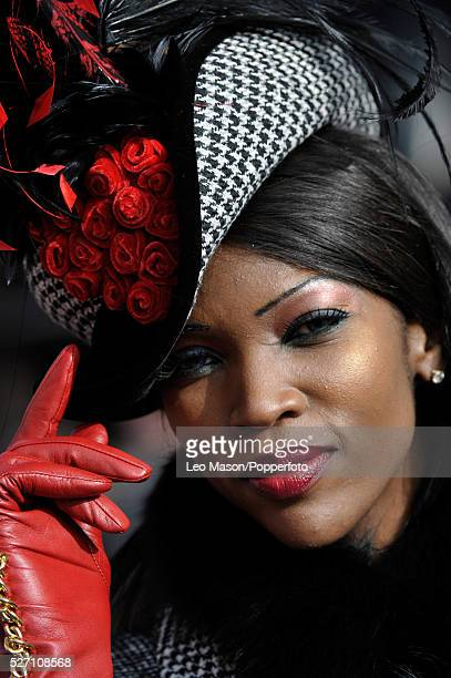 View of a female racing fan pictured wearing a hat and red gloves on Ladies Day during the 2012 Cheltenham National Hunt Festival at Cheltenham...