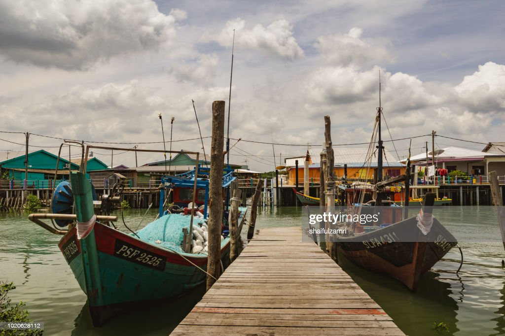 A view of a fishermen's village on stilts besides the sea in Pulau Ketam (Crab Island). Majority of the community in here works as fisherman or related activities such as producing sea food products or manage a sea food restaurants. : Stock Photo