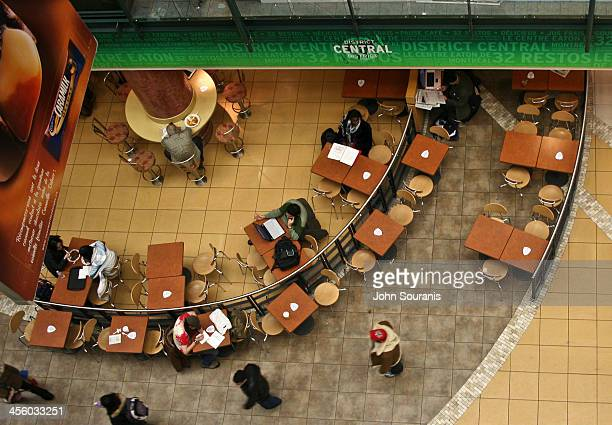 View of a food court in a downtown shopping mall taken from an upper floor. It shows people eating, working on a computer and walking by.