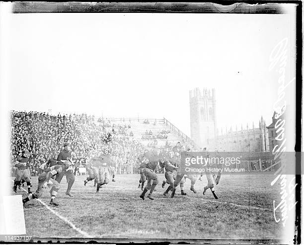 View of a football player holding a football running on the field during a football game between the University of Chicago and Northwestern...