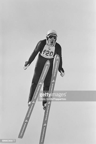 View of a forerunner pictured in action to test the course prior to competition in the Men's normal hill individual ski jumping event at the 1980...