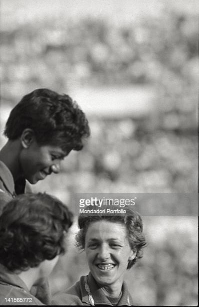 View of a foreshortening of the three smiling athletes on the olumpic podium of the 100 feminine metres with the British Dorothy Hyman the US Wilma...