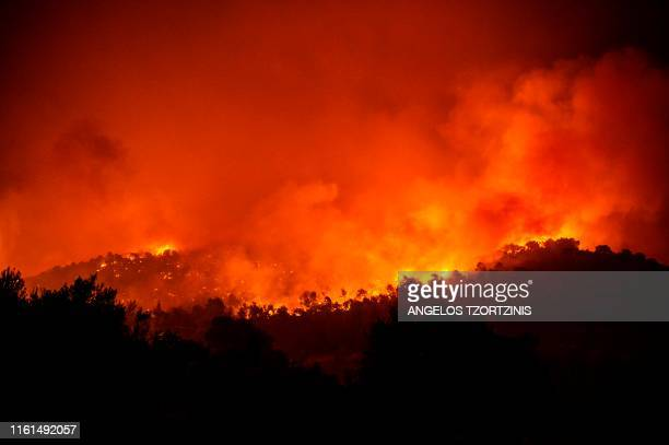 TOPSHOT View of a forest fire near the village of Makrimalli on the island of Evia northeast of Athens on August 13 2019 Hundreds of villagers were...