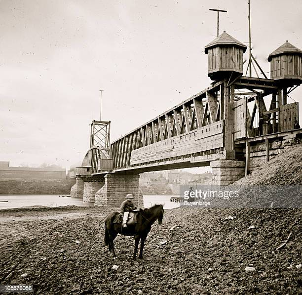 View of a fortified railroad bridge across the Cumberland River in Nashville TN 1864 A young boy sits on a horse on the river's near bank