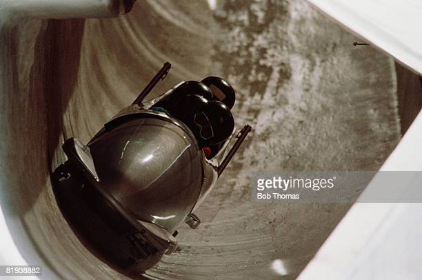 View of a fourman bobsleigh team in practice prior to competition in the bobsleigh event at Canada Olympic Park during the 1988 Winter Olympics in...