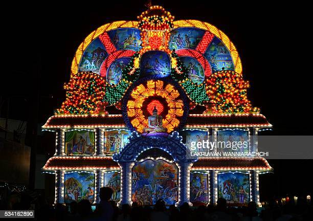 TOPSHOT A view of a giant display featuring a seated Buddha during the annual Vesak Buddhist festival celebrations in Colombo on May 25 2016 Sri...