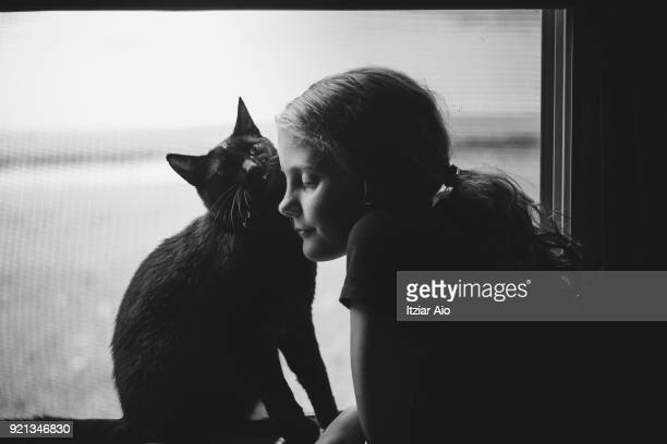 view of a girl at  window with her cat. - amour noir et blanc photos et images de collection
