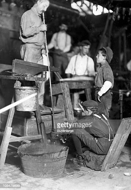 View of a glass blower and mold boy at Seneca Glass Works in Morgantown West Virginiia 1908 The glass blower manipulates the glass by blowing air...