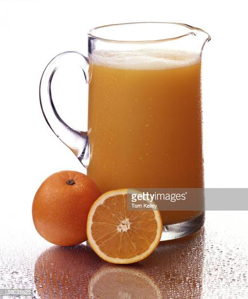 View of a glass pitcher of orange juice with a pair of oranges next to it one halved 2001